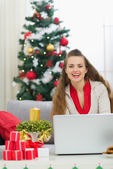 Smiling young woman near Christmas tree sending greeting emails — Stock Photo