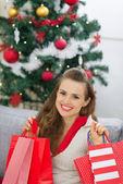 Glückliche junge frau in der nähe von weihnachtsbaum mit einkaufstüten — Stockfoto
