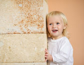 Portrait of baby leaning against wall — Stock Photo