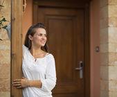 Heureuse femme debout sur le pas de porte et de la recherche sur l'espace de la copie — Photo