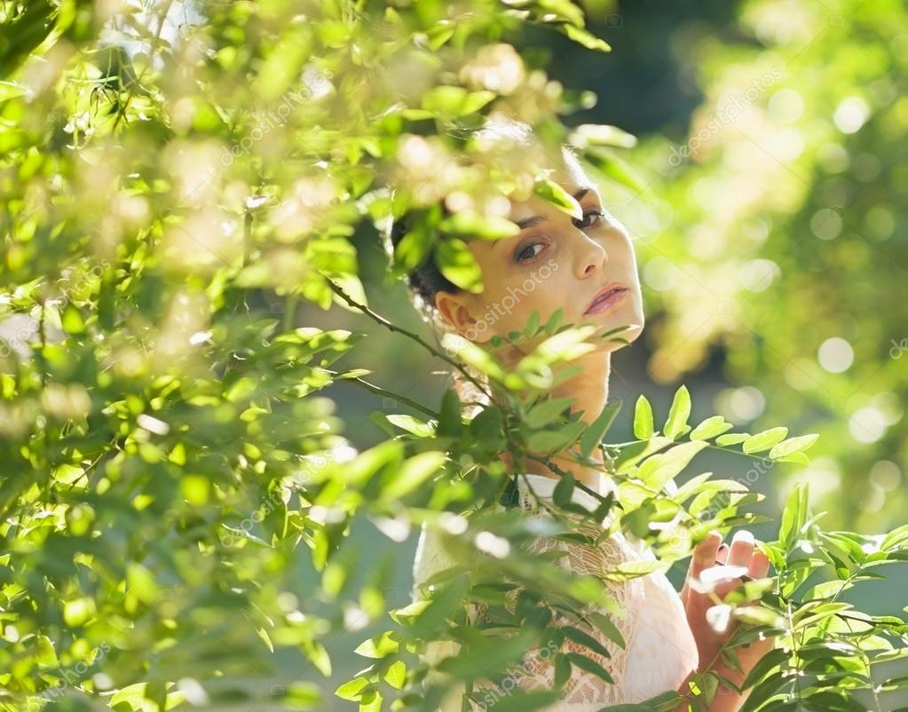 Portrait of young woman hiding in foliage — Stock Photo #13725690