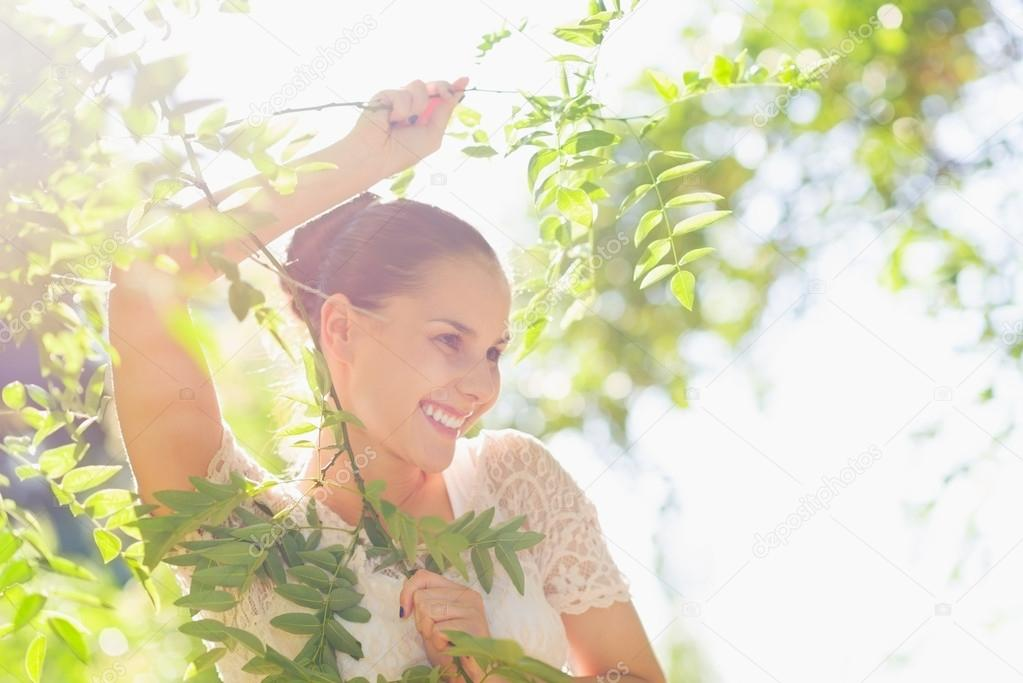 Portrait of young woman in foliage looking on copy space — Stock Photo #13725744
