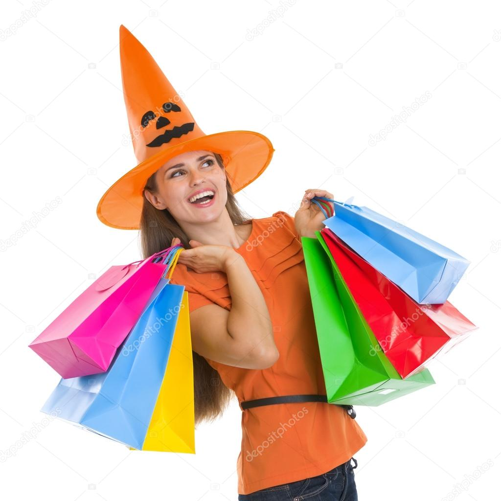 Happy woman in Halloween hat with shopping bags looking on copy space — Stock Photo #13728365
