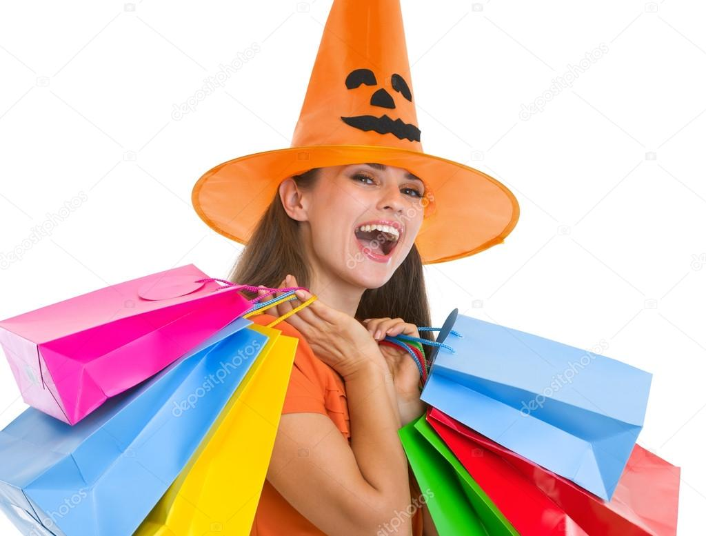 Happy young woman in Halloween hat with shopping bags — Stock Photo #13728395