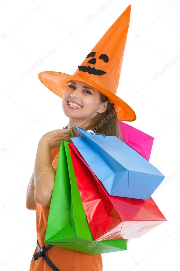 Portrait of happy young woman in Halloween hat with shopping bags — Stock Photo #13728404