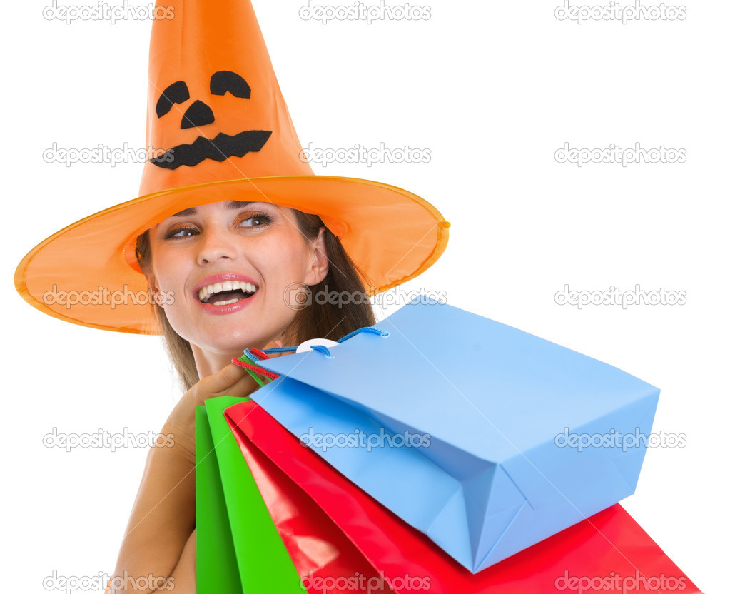 Happy woman in Halloween hat with shopping bags looking on copy space — Stock Photo #13728405