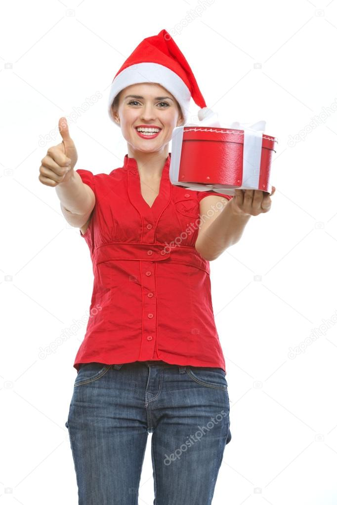 Smiling woman in Santa hat with Christmas present box showing thumbs up — Stock Photo #13728504