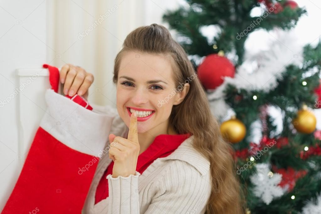 Smiling young woman put gift in Christmas socks and showing shh gesture  Stock Photo #13729283