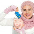 Happy woman in knit winter clothing putting credit card in piggy - Stock Photo