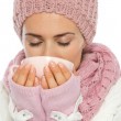 Woman in knit scarf, hat and mittens drinking hot beverage — Stock Photo #14919939