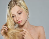 Portrait of blond girl checking hair ends — Stock Photo