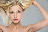 Portrait of blond girl rising up hair — Stock Photo
