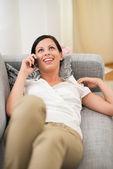 Glad ung kvinna på divan och talande mobiltelefon — Stockfoto