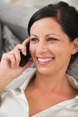 Happy young woman laying on sofa and speaking mobile phone — Stock Photo