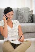 Šťastná mladá žena mluvící mobil a psaní v poznámkovém bloku — Stock fotografie