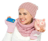 Smiling woman in knit winter clothing holding credit card and pi — Stock Photo
