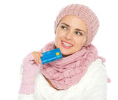 Thoughtful woman in knit winter clothing holding credit card — Stock Photo