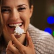 Happy woman eating Christmas cookie in front of Christmas lights — Stock Photo #14924227