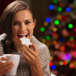 Happy woman eating Christmas cookie and drinking hot chocolate — Stock Photo #14924265