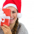 Smiling woman in Santa hat holding Christmas present — Stock Photo