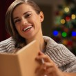 Happy woman in front of Christmas tree reading book — Stock Photo