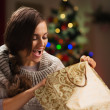 Happy woman in front of Christmas tree looking in shopping bag — Stock Photo #14923359