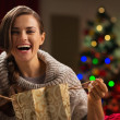 Happy woman with shopping bag in front of Christmas tree — Stock Photo #14923415