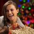 Smiling woman with shopping bag in front of Christmas lights — Stock Photo #14923515