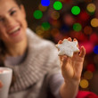 Closeup on hand holding Christmas cookie and happy woman in back — Stock Photo #14924255