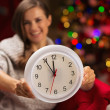 Closeup on clock in hand of happy woman in front of Christmas tr — Stock Photo #14924433