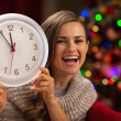 Happy woman showing clock in front of Christmas tree — Stock Photo #14924445
