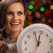 图库照片: Portrait of happy woman showing clock in front of Christmas ligh