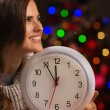 Portrait of happy woman showing clock in front of Christmas ligh — Stockfoto