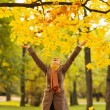 Happy woman throwing fallen leaves — Stock Photo