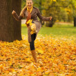 Cheerful woman kicking fallen leaves — Stock Photo