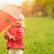 Smiling baby looking out from red umbrella — Stock Photo