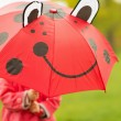 Baby hiding behind red umbrella — Stock Photo