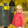Portrait of baby near trash can — Stock Photo