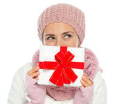 Thoughtful woman in knit winter clothing hiding behind Christmas — Stock Photo