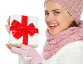 Smiling woman in knit winter clothing holding Christmas present — Stock Photo