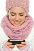 Happy woman in knit winter clothing writing text message — Stock Photo