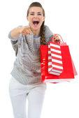 Mujer en jersey con bolsas de la compra señalando en cámara — Foto de Stock