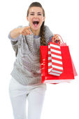 Woman in sweater with shopping bags pointing in camera — Stock Photo