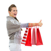 Happy woman in sweater showing thumbs up with shopping bags — Stock Photo