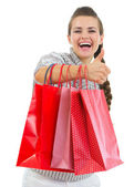 Smiling woman in sweater showing thumbs up with shopping bags — Stock Photo