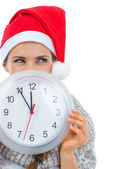 Woman in Santa hat holding clock in front of face and looking on — Stock Photo