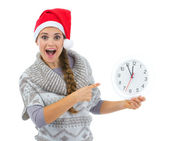 Surprised woman in Santa hat pointing on clock — Stock Photo