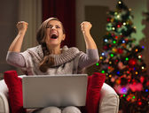 Happy woman with laptop rejoicing success in front of Christmas — Stock Photo