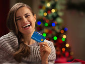 Smiling woman in front of Christmas tree holding credit card — Stock Photo