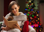 Woman in chair in front of Christmas tree reading book — Stock Photo